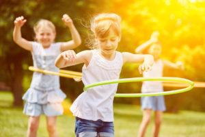 Glückliche multikulturelle Gruppe Kinder spielt im Sommer